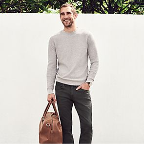 Man wearing jeans holding a bag