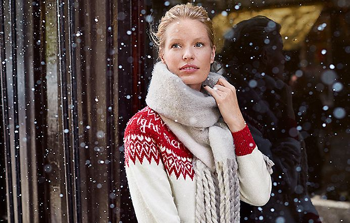 Woman in the snow wears a grey scarf and white and red Christmas jumper