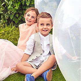 A boy and girl at a wedding wearing M&S occassionwear