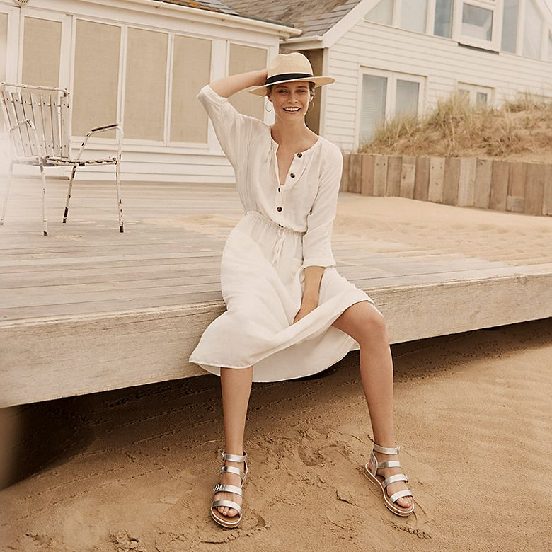 Woman wearing white linen dress with metallic sandals and fedora hat