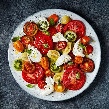 A plate of sliced M&S Isle of Wight tomatoes with buffalo mozzarella, basil and olive oil