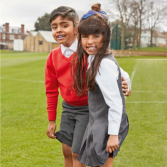 Girl and boy wearing M&S school uniform standing in a field