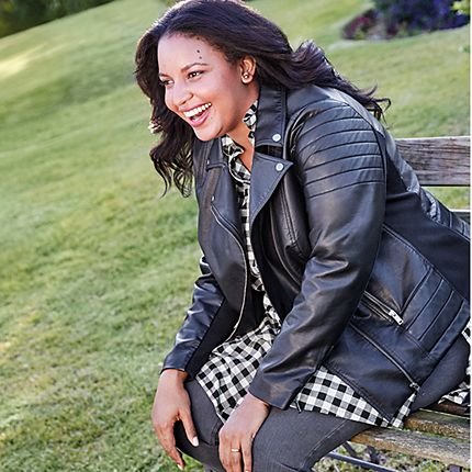 Model wearing a black faux-leather biker jacket, a black and white checked shirt and grey jeans from the Curve collection