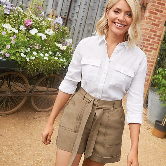 Holly Willoughby wearing a white linen shirt and khaki linen-blend shorts