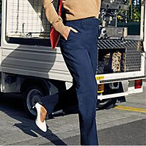 Woman in road wearing a beige jumper, navy trousers, red bag and white heels