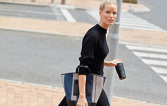 Woman wears a black knitted top and skirt and colour-block handbag