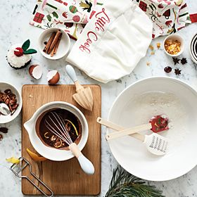 Mixing bowls and kitchen utensils with Christmas baking ingredients