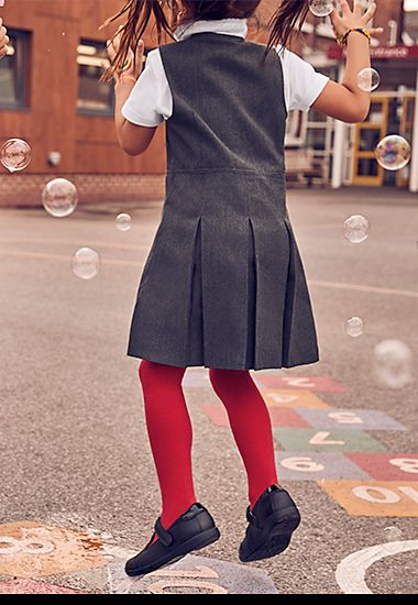 Girl wearing M&S school uniform grey pinafore
