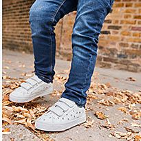 Boy wears mid-wash skinny jeans with white trainers