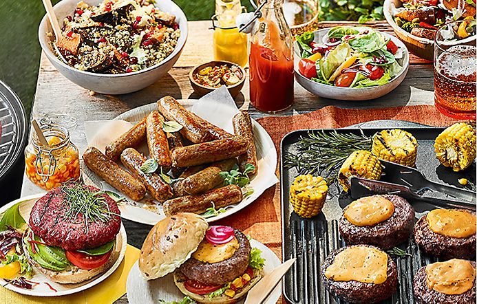 Selection of barbecue burgers, sausages, salads and sauces