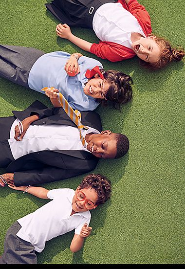 Kids lying in a school field wearing M&S school uniform