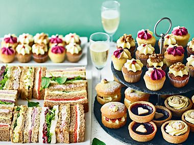 Spread of sandwiches, cakes and champagne