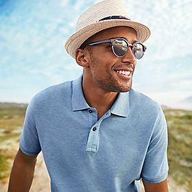 A man wearing a straw hat and polo shirt on the beach